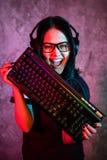 Bella ragazza professionale del Gamer con la tastiera Vetri d'uso e sorridere del geek sveglio casuale Internet cyber di e-sport fotografia stock libera da diritti