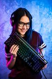 Bella ragazza professionale del Gamer con la tastiera Vetri d'uso e sorridere del geek sveglio casuale Internet cyber di e-sport fotografia stock