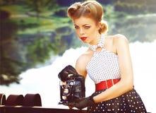 Bella ragazza in retro vestito con la retro macchina fotografica vicino al vodoema immagini stock libere da diritti