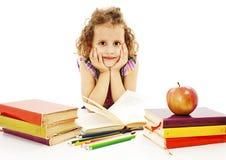 Bella ragazza riccia con i libri di banco sulla tabella Immagini Stock Libere da Diritti