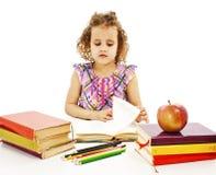 Bella ragazza riccia con i libri di banco sulla tabella Fotografia Stock Libera da Diritti
