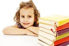 Bella ragazza riccia con i libri di banco sulla tabella Immagini Stock