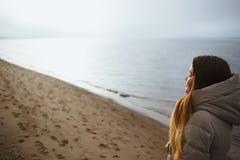 Bella ragazza in rivestimento di inverno che si rilassa con gli occhi chiusi al tramonto di inverno dal fiume Immagini Stock Libere da Diritti