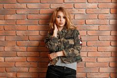 Bella ragazza in rivestimento militare vicino al muro di mattoni rosso fotografie stock libere da diritti