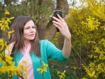 Bella ragazza in rivestimento verde che fa selfie fra l'albero giallo del fiore Immagine Stock
