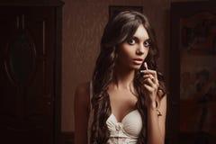 Bella ragazza in rossetto del veste da camera, guardante nello specchio Immagini Stock