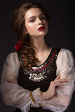 Bella ragazza russa in vestito nazionale con un'acconciatura della treccia e le labbra di rosso Fronte di bellezza fotografia stock