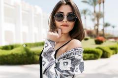 Bella ragazza sensuale che posa toccando il suo fronte con la mano, camminante giù la via su fondo esotico attraente immagine stock