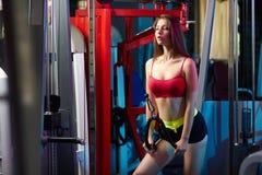 Bella ragazza sensuale femminile attraente che fa allenamento di forma fisica con la macchina del cavo alla palestra Fotografie Stock Libere da Diritti