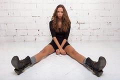 Bella ragazza seria che si siede sul pavimento e che esamina la macchina fotografica Muro di mattoni bianco, non Immagini Stock Libere da Diritti