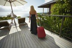 Bella, ragazza sessuale che cammina attraverso l'area di stagno con la borsa dei bagagli Immagine Stock