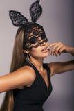 Bella ragazza sexy con capelli diritti lunghi nella maschera nera del coniglietto del pizzo immagini stock