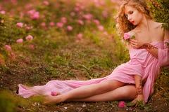 Bella ragazza sexy in un vestito rosa che sta nelle rose del giardino fotografia stock