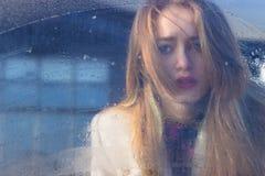 Bella ragazza sola abbastanza triste triste di seksalnaya dietro vetro bagnato con i grandi occhi tristi in un cappotto fotografia stock