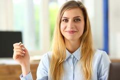 Bella ragazza sorridente alla penna dell'argento della tenuta del posto di lavoro Immagine Stock Libera da Diritti