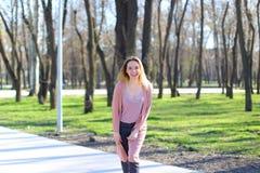 Bella ragazza sorridente che esamina macchina fotografica e che cammina nel parco di primavera Fotografia Stock