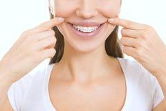 Bella ragazza sorridente con il fermo per i denti che indica alla sua s fotografia stock