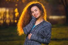 Bella ragazza sorridente con riccio, capelli illuminati dal sole fotografia stock