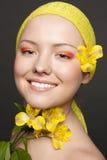 Bella ragazza sorridente con un fiore giallo fotografie stock