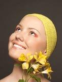 Bella ragazza sorridente con un fiore giallo immagini stock