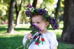 Bella ragazza sorridente in corona dei fiori in prato sulla d soleggiata Fotografia Stock