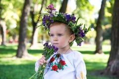 Bella ragazza sorridente in corona dei fiori in prato sulla d soleggiata Fotografia Stock Libera da Diritti