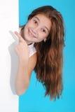 Bella ragazza sorridente felice che mostra insegna o copyspace in bianco per lo slogan o il testo Fotografie Stock