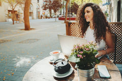 Bella ragazza sorridente riccia che lavora al computer portatile in caffè Immagine Stock Libera da Diritti