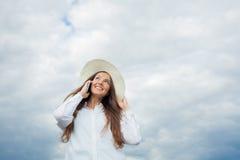 Bella ragazza sorridente in un cappello bianco con un ampio bordo che parla sul telefono su fondo delle nuvole di tempesta Fotografia Stock