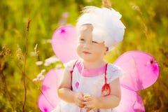 Bella ragazza spensierata che gioca all'aperto nel campo con l'alto gree Fotografia Stock Libera da Diritti