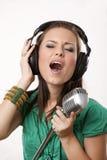 Bella ragazza stupefacente con il microfono dello studio Fotografia Stock