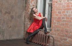 Bella ragazza su un davanzale della finestra fotografie stock libere da diritti