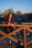 Bella ragazza su un ponte di legno al tramonto immagine stock