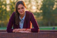Bella ragazza su un ponte di legno al tramonto fotografia stock libera da diritti