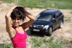 Bella ragazza sui precedenti della sua automobile Immagine Stock Libera da Diritti