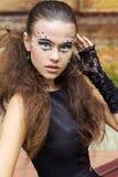 Bella ragazza sui precedenti delle foglie nel giorno di autunno sulla via con trucco di fantasia in un vestito nero Immagini Stock Libere da Diritti