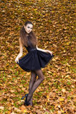 Bella ragazza sui precedenti delle foglie nel giorno di autunno sulla via con trucco di fantasia in un vestito nero Fotografia Stock