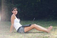 Bella ragazza sul Internet alla sosta Fotografie Stock