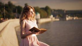 Bella ragazza sul lungomare con un libro in loro mani stock footage