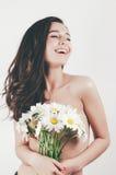 Bella ragazza sveglia tenera di estate con la pelle perfetta dell'ente topless tiene i fiori dei camomiles Priorità bassa bianca fotografia stock libera da diritti