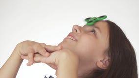 Bella ragazza teenager allegra che fila un filatore verde di irrequietezza sulla sua fronte su fondo bianco Fotografia Stock Libera da Diritti