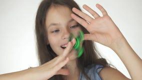 Bella ragazza teenager allegra che gioca con il filatore verde di irrequietezza su fondo bianco Immagini Stock