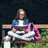 Bella ragazza teenager bionda in camicia dei jeans che legge un libro sul banco con uno zaino e un pattino nel parco Immagini Stock