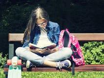 Bella ragazza teenager bionda in camicia dei jeans che legge un libro sul banco con uno zaino e un pattino nel parco Immagine Stock