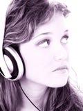 Bella ragazza teenager che ascolta le cuffie nei toni dell'uva Immagini Stock