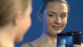 Bella ragazza teenager che fa le foto del selfie sullo smartphone davanti allo specchio archivi video
