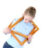 Bella ragazza teenager che gioca con le cornici vuote sopra bianco Fotografie Stock