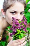 Bella ragazza teenager che sente l'odore dei fiori lilla Fotografie Stock