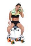 Bella ragazza teenager che si siede sul banco di allenamento sopra bianco Fotografie Stock
