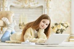 Bella ragazza teenager che si trova sul pavimento e che per mezzo del computer portatile Fotografia Stock